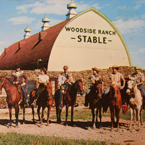 People On Horses In Front Of The Stable